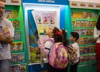 Crianças folheiam o 'maior gibi do mundo' em área dedicada à 'Turma da Mônica' no estande da Maurício de Souza Produções em parceria com a Panini durante a Bienal do Livro de SP — Foto: Fábio Tito/G1